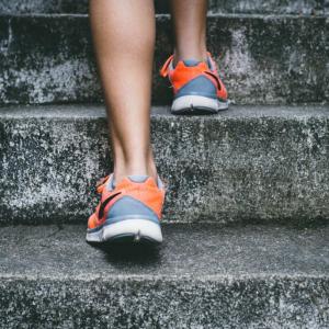 Kvinde i løbesko der løber op ad en trappe