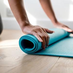 Yogamåtte der bliver rullet sammen af en kvinde